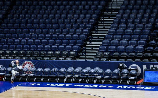 Rob Thomas, an employee with CSE Sports, talks on the phone from a team bench after the SEC announced Thursday morning the cancellation of the 2020 SEC men's college basketball tournament at Bridgestone Arena, one of a number of major events canceled in response to the coronavirus. The SEC Conference announced the cancellation of the 2020 SEC Men's College Basketball Tournament after the COVID-19 outbreak. March 12, 2020.