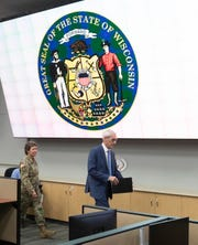 Gov. Tony Evers, right, arrives at a briefing last week to discuss updates to the state's response to the coronavirus pandemic. With Evers is Brig. Gen. Joane Mathews, Wisconsin's deputy adjutant general for Army.