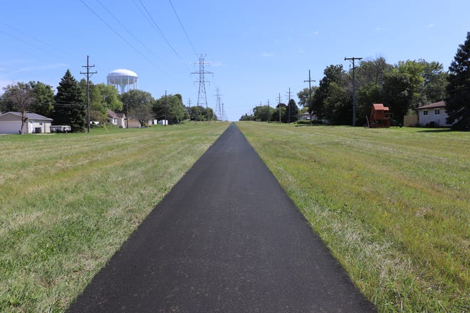 A projected image shows what the new Powerline Trail would look like along the We Energies power line corridor in Greenfield. Phase 1 of the shared-use, east-west recreational path will connect to the Oak Leaf Trail at 105th Street and Cold Spring Road and run east to 60th Street. This view looks east from 92nd Street.
