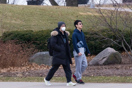 A masked pedestrian walks near Camp Randall Stadium on the campus of UW-Madison on Thursday. The university is one of multiple Wisconsin universities that took dramatic steps to ward off or curb the spread of the COVID-19 outbreak.
