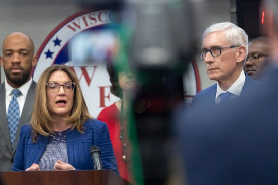 Wisconsin Department of Health Services (DHS) Secretary  Andrea Palm, left,  speaks as Gov. Tony Evers looks on at a briefing to discuss updates to the state's response to the coronavirus pandemic.