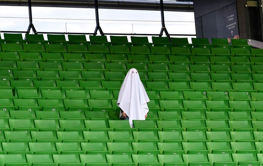 A man dressed as a ghost stands on the empty tribune prior the Europa League round of 16 first leg soccer match between Linzer ASK and Manchester United in Linz, Austria, Thursday, March 12, 2020. The match is being played in an empty stadium because of the coronavirus outbreak.