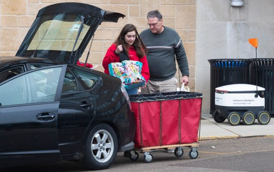 A woman moves out of Chadbourne Hall Thursday on the campus of UW-Madison. The university is one of multiple Wisconsin universities that took dramatic steps to ward off or curb the spread of the COVID-19 outbreak, everything from moving courses online to canceling university-sponsored travel and events to extending spring break.