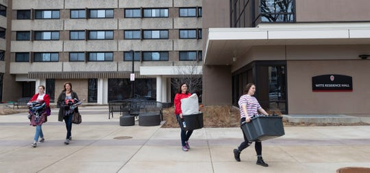 Calli Fiez, right, and her mother, Kim, carry her belongings to their car while moving out of Witte Residence Hall on the campus of UW-Madison on Thursday. The university is one of multiple Wisconsin universities that took dramatic steps to ward off or curb the spread of the COVID-19 outbreak.