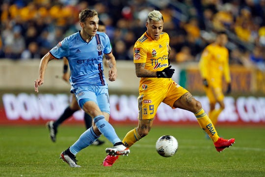New York City FC midfielder James Sands passes the ball past Tigres forward Eduardo Vargas (9) during the first half in the first leg of a quarterfinal in the CONCACAF Champions League soccer tournament Wednesday, March 11, 2020, in Harrison, N.J. (AP Photo/Adam Hunger)