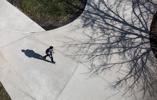 A student is shown walking outside Teachers College at Ball State University after the university switched from in-person to virtual classes, but before campus housing was closed.