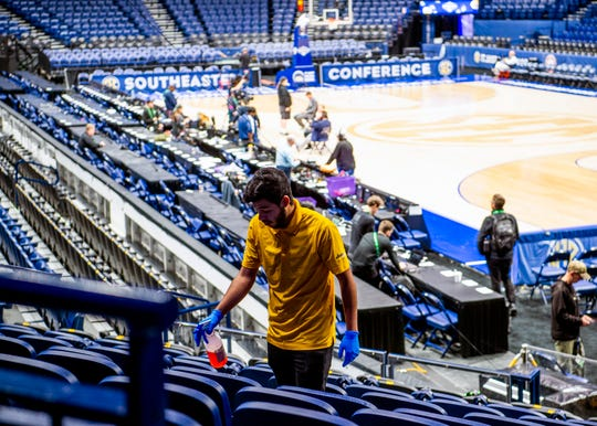 Workers begin to disinfect seats inside Bridgestone Arena after the Southeastern Conference decided to cancel the SEC Tournament over coronavirus concerns on Thursday, March 12, 2020.