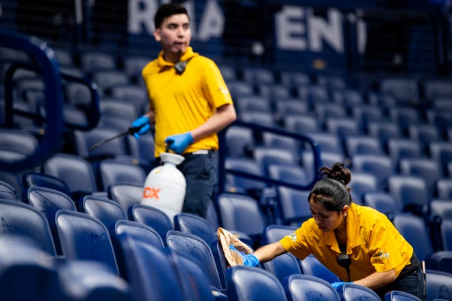 Stadium workers clean seats after it was announced that the Southeastern Conference Tournament was canceled due to Coronavirus concerns at Bridgestone Arena in Nashville, Tenn., Thursday, March 12, 2020.