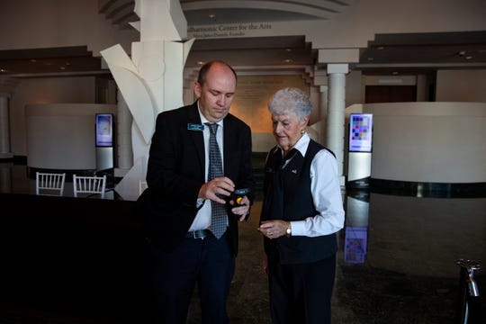 Front of House Manager at Artis-Naples Jeremy Tipton, left, shows usher Jean Kmon how to use a ticket scanner, during a set-up demonstration, Thursday, March 12, 2020, at Artis—Naples' Hayes Hall