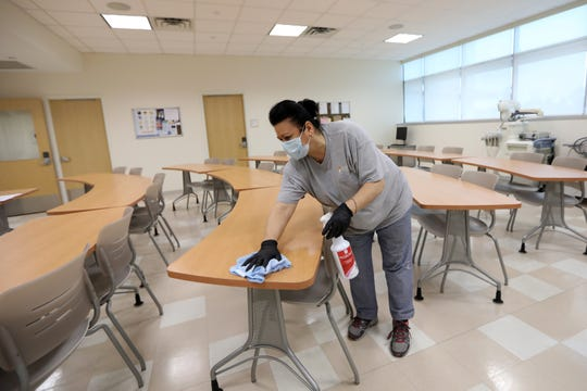 Raymond Bilalaj cleans a classroom at Health Professions Integrated Teaching Center, at Bergen Community College, in Paramus  Students are currently on spring break and were originally scheduled to return on March 16.  They are currently scheduled to return on March 23 instead, a date which could be pushed back again, amongst coronavirus concerns. Thursday, March 12, 2020