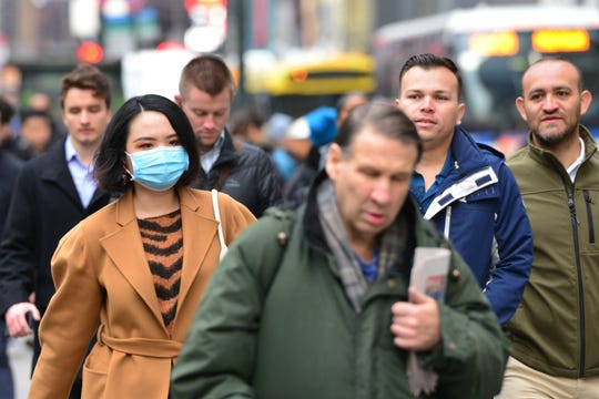 A woman walks along 42nd St wearing a face mask in New York City, N.Y. on Thursday March 12, 2020.