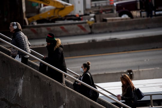 Commuters including a woman in a face mask ascend stairs to Lemoine Avenue in Fort Lee.