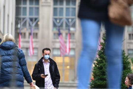 A man wearing a face mask walks through Rockefeller Square in New York City, N.Y. on Thursday March 12, 2020.