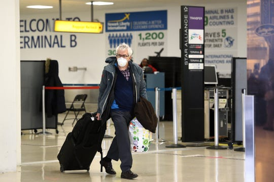 Passengers arriving at Newark Liberty International Airport take precautions against the coronavirus COVID-19 on Thursday, March 12, 2020, ahead of a 30-day travel ban from Europe, imposed by President Trump, that goes into effect on Friday.