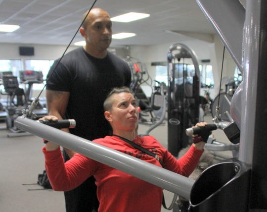 Trainer Gabe Dominguez of Gabe's Fitness in Deming, looks on during Beth King's routine workouts.