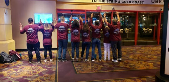 Ancelmo Encinias, Gerry Brown-Encinias, Michael Rodriguez, Maria Rodriguez, Elena Glaze, Joe Glaze, Trish Alvarez and Jose Alvarez pose with their custom made shirts at the WAC tournament in Las Vegas, Nevada.