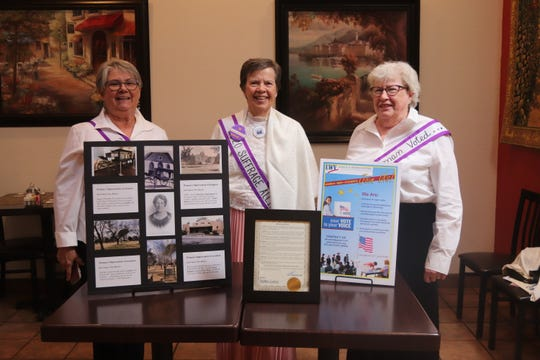 Shown here behind some historical information is a co-president Eileen VanWie, center, Marjorie Burr one of the main speakers, right, and Maryellen Kebbel a director of the organization, left.
