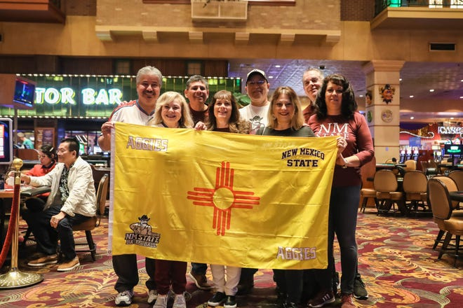 A group of Aggie fans of Las Cruces pose in front of a New Mexico flag after the WAC announced that the rest of the conference tournament has been cancelled due to coronavirus concerns in Las Vegas, Nevada, on Thursday, March 12, 2020.