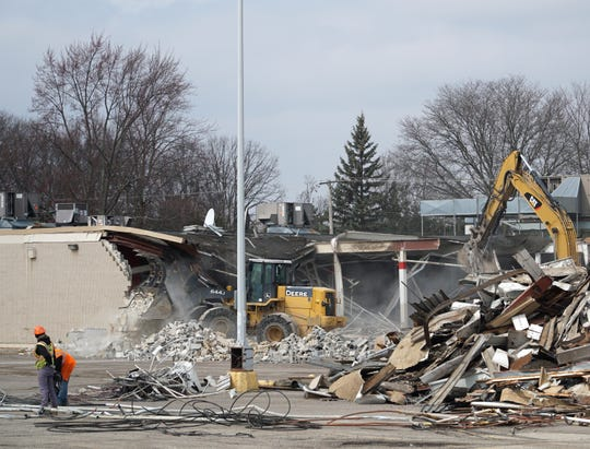 As a backhoe grabs pieces of steel beam a bulldozer punches a dusty hole in the wall of the former Garden City Kmart - the first store opened in the U.S. in 1962. The site is at Ford and Middlebelt Road.