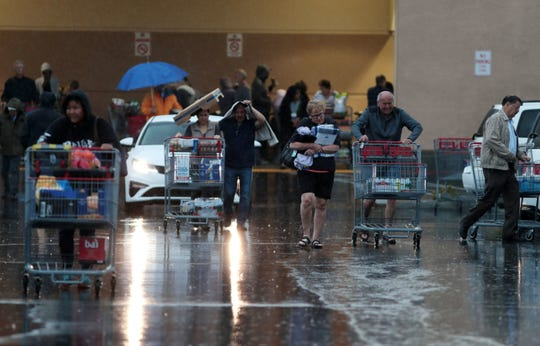 Shoppers navigate the crowded parking lot during a rainy day at Costco in Palm Desert on Thursday, March 12, 2020. Consumers in the valley and across California have swarmed stores, creating shortages of items like bottled water, sanitizers and toilet paper.