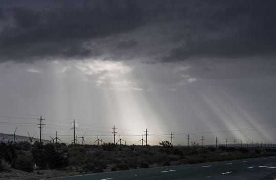 The sun shines through the clouds briefly as rain falls on the Coachella Valley in north Palm Springs, March 12, 2020.