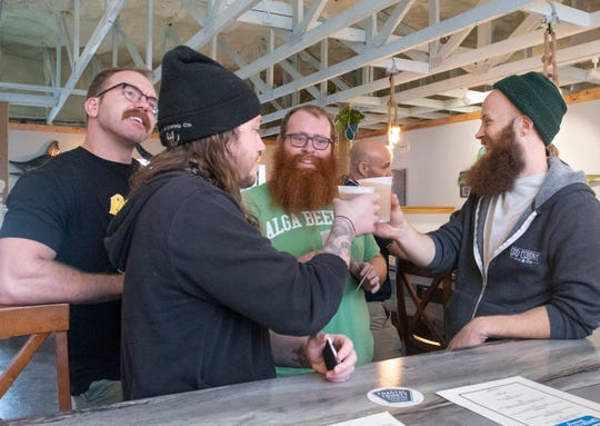 From left, Rhomas Grier of Alga Beer Co., Ryan Brei of Odd Colony Brewing Co., Brett Reid of Alga Beer Co. and Brett Schweigert of Odd Colony Brewing Co. toast during the soft opening at Coastal County Brewing Co. on Wednesday.