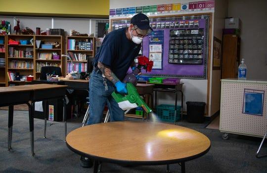 Robert Truman (SSC Services for Education) uses an electrostatic sprayer to sanitize a classroom, March 12, 2020, at Kyrene de la Mirada Elementary School, 5500 W Galveston St., Chandler.