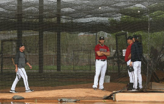 Arizona Diamondbacks pitcher Madison Bumgarner (center right) stands in batting case at their Cactus League spring training camp on Mar. 12, 2020 at Salt River Fields at Talking Stick in Scottsdale, Ariz.