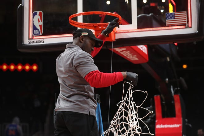 A State Farm Arena staff member removes the basketball net from a hoop after an Atlanta Hawks overtime loss to the New York Knicks at State Farm Arena. The NBA suspended further play Wednesday night due to concerns over the spread of the novel coronavirus, COVID-19.