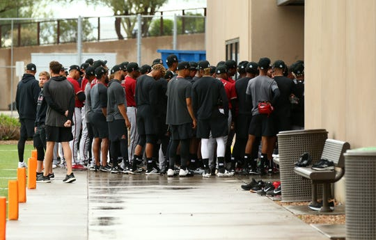Arizona Diamondbacks minor league players huddle outside their clubhouse after a shortened practice session at their Cactus League spring training camp on Mar. 12, 2020 at Salt River Fields at Talking Stick in Scottsdale, Ariz.
