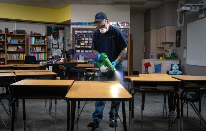 Robert Truman, with SSC Services for Education, uses an electrostatic sprayer to sanitize a classroom on March 12, 2020, at Kyrene de la Mirada Elementary School in Chandler.