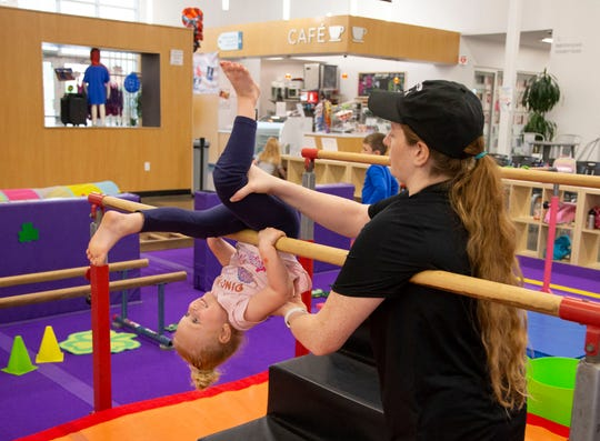 Coach Emily Thomas assists Blake Johnson, 4, at Arizona Sunrays Learning Center, a preschool that is an off-shoot of a 30-year-old gymnastics and dance center, in Phoenix on March 11, 2020.