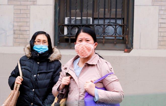 Personas con máscaras protectoras caminan por el barrio chino de Nueva York, Nueva York, Estados Unidos.