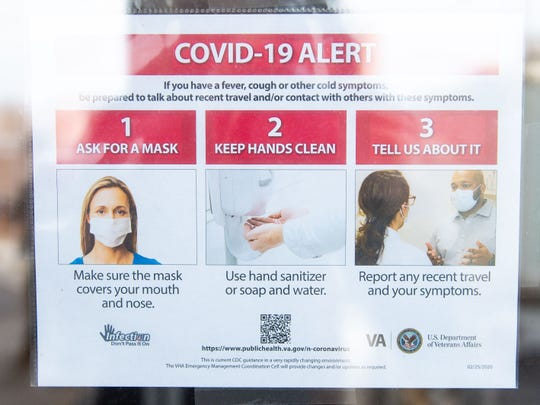 Posters are hung up around the Lebanon Veterans Affairs Medical Center telling those with coronavirus symptoms what to do.