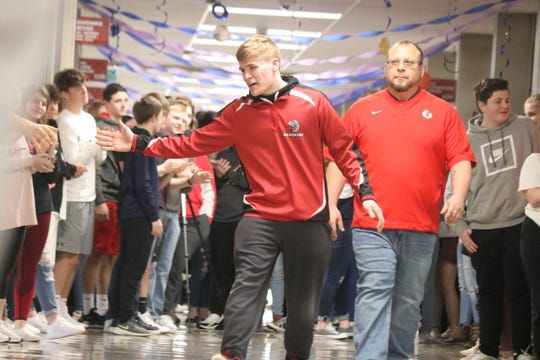 Port Clinton senior wrestler Mason Elson offers high fives as his peers cheer him on Thursday before he heads to the state championship tournament in Columbus.