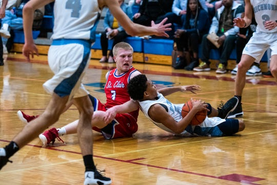 St. Clair's Sean Donaldson (3) and Richmond's Marcus Thompson go down fighting for the ball during the MHSAA Division 2 district final Wednesday, March 11, 2020, at St. Clair High School.