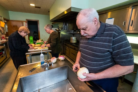 Pete Jungquist, right, peels a potato Wednesday, March 11, 2020, at Grace Episcopal Church in Port Huron.