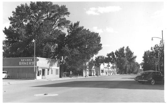 The Nevada Bakery, originally known as the Downey Saloon or Exchange, was replaced by the southern section of the Yerington Inn. The Lee house would have been about 100 feet further back from where the Chevron sign is located on the right side of the picture. The view is looking southeast down Main Street. City hall can be seen at the end of the business buildings.
