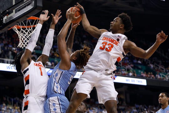 Syracuse forward Elijah Hughes (33) and forward Quincy Guerrier (1) block North Carolina forward Armando Bacot (5) during the first half of an NCAA college basketball game at the Atlantic Coast Conference tournament in Greensboro, N.C., Wednesday, March 11, 2020. Syracuse won 81-53.