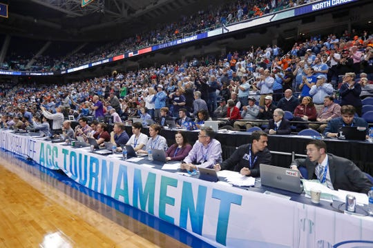 Fans and media watch during an NCAA college basketball game between North Carolina and Syracuse at the Atlantic Coast Conference tournament in Greensboro, N.C., Wednesday, March 11, 2020. The ACC announced it will close the remainder of its men's basketball tournament to spectators, beginning with Thursday's quarterfinals, amid the emerging threat of the spread of the coronavirus.