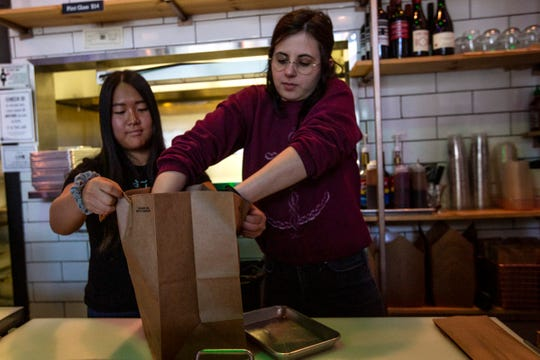 Bo & Vine employees Yena Lee and Lily Pro prepare a to-go order at their location in downtown Salem on March 12, 2020.