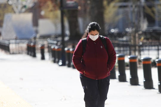 A passerby in a mask walks in front of Gill Coliseum on Oregon State University campus on March 12, following the cancellation of the OSAA State Basketball Tournament.