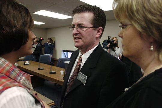 Senator Dan Sutton talks with Lana Sanner, left, and his wife, Mary Beth, after the committee went into recess during his 2007 Senate disciplinary hearing.