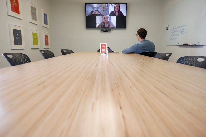 Jarad Johnson, president of Mostly Serious, holds a virtual meeting with account manager Emily Coulter Dunn, top right, and senior designer Jessica Gottstein on Thursday, March 12, 2020.