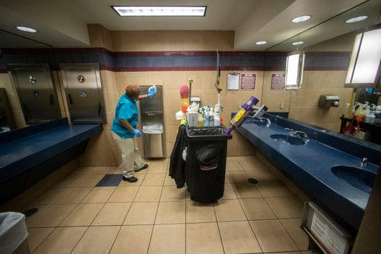 A custodial worker wipes down surfaces inside a bathroom at the Tallahassee International Airport, Thursday, March 12, 2020.
