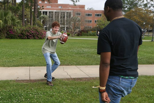 Brett Raley, left, and Isaac Bradley, Chi Alpha Campus Ministry members visiting Florida State University from Troy University, play catch with a football at FSU Thursday, March 12, 2020, one day after it was announced that March 23, after spring break, classes would be moved online for at least two weeks in response to concerns about the spread of coronavirus.