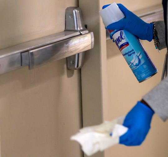 A custodial worker sprays Lysol on a door at the Tallahassee International Airport, Thursday, March 12, 2020.
