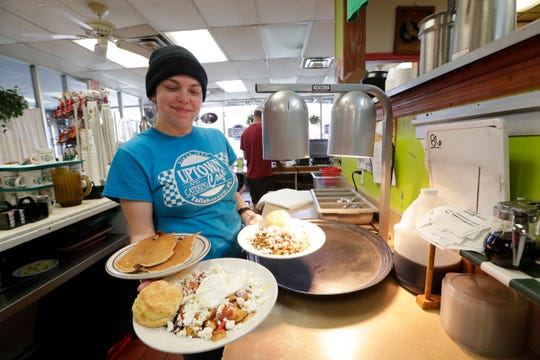 Uptown Cafe server Dianna White picks up three plates of food from the window Thursday, March 12, 2020. Business at the restaurant has remained steady, but Uptown Cafe has had customers cancel their catering orders in the past few days as events are canceled due to coronavirus concerns.
