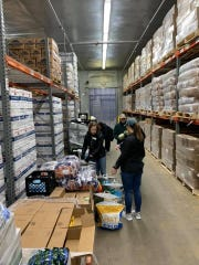 """Volunteers help prepare boxes of food to go to families who are """"food insecure"""" in Leon County during spring break, 2020."""