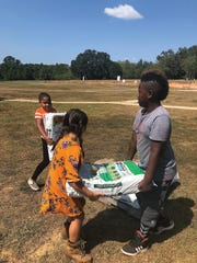 Second graders tote bags of soil to the new gardens at Conley. They are Summer Colston, back,and Briley Rowan and Keyunn Wright.